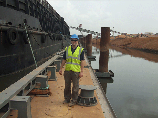 AJ Power Senior Electrical and Electronic Engineer Eugene Devlin, pictured with the barge that transports the iron ore to the Atlantic Ocean.